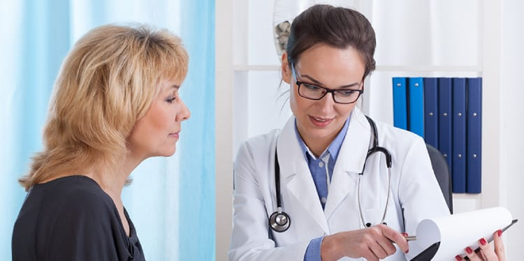 Image of a female doctor reading a chart to an adult female patient