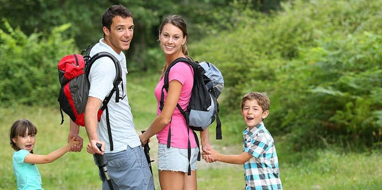 Family picture, husband, wife, young boy and girl smiling while walking in the park